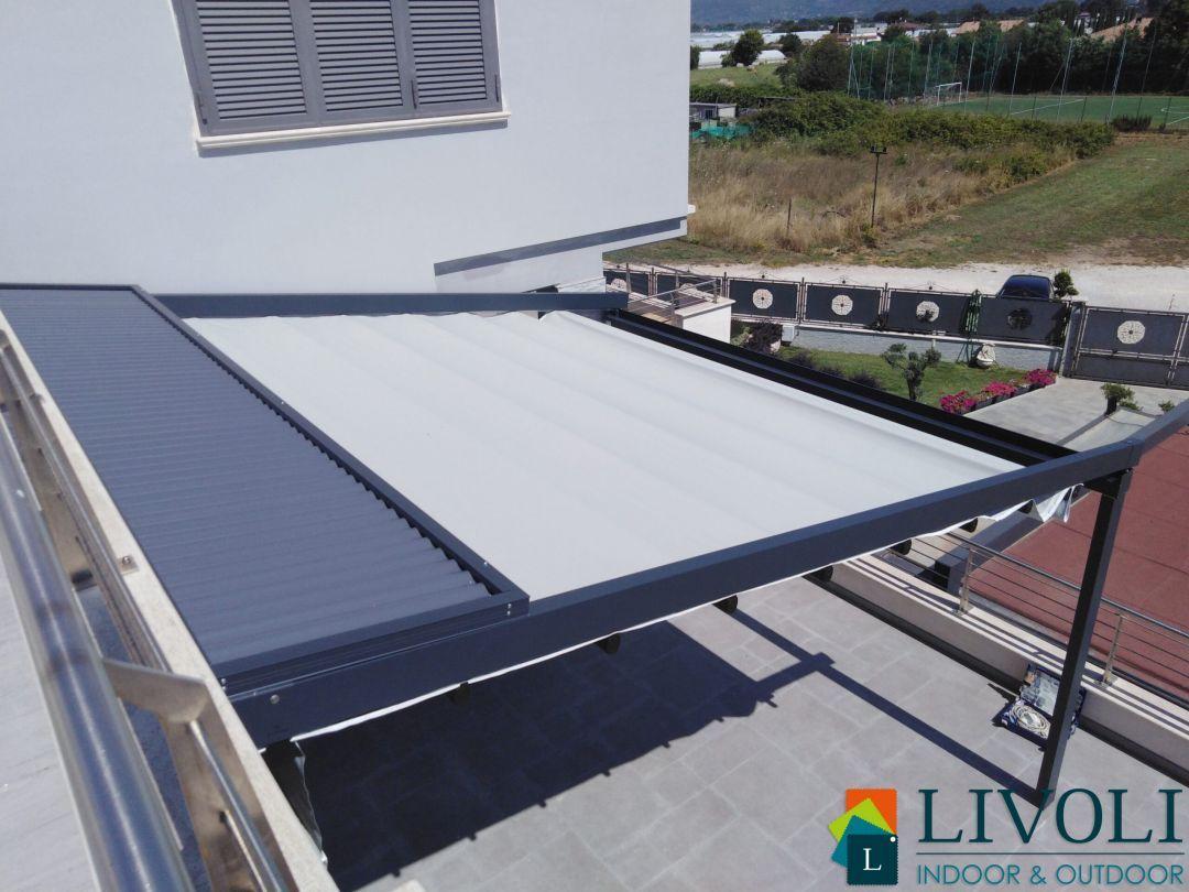 Pergotenda addossata con copertura retrattile ad impacchettamento in PVC, struttura in alluminio, tettuccio di protezione, radiocomando ed illuminazione led integrata.
