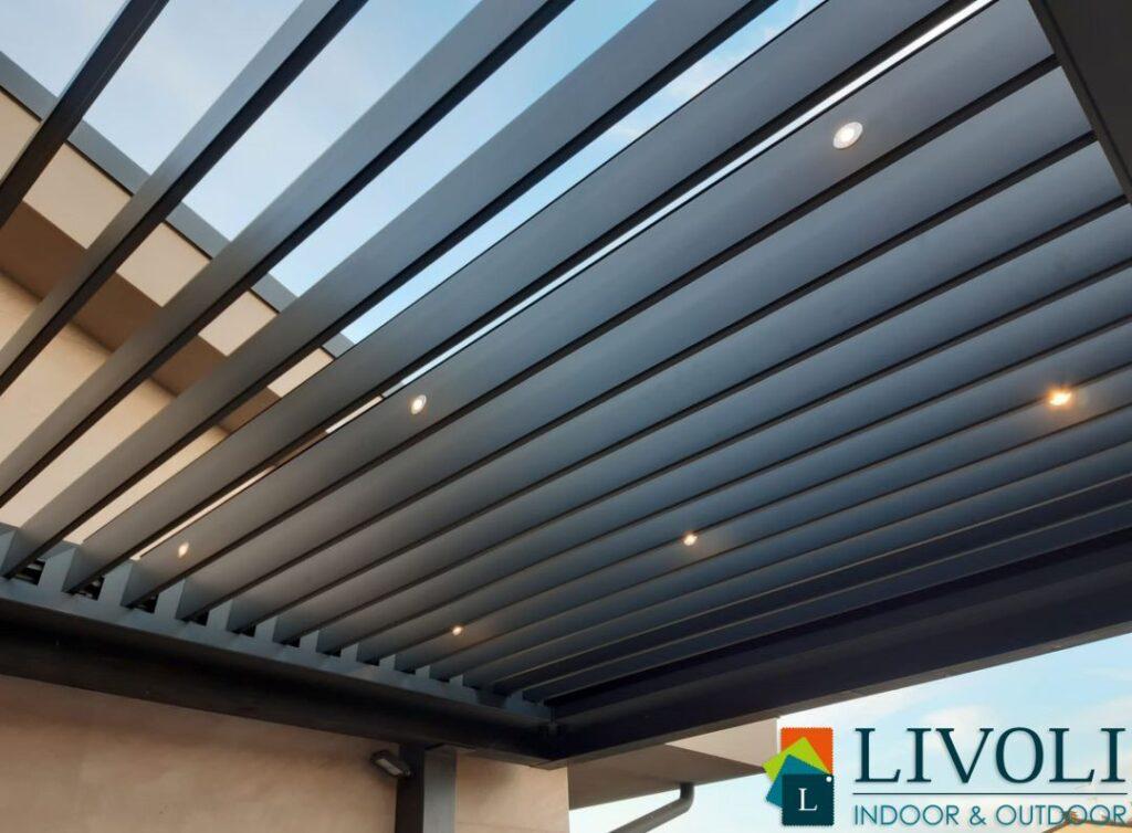 Pergola Bioclimatica in alluminio, installata su struttura esistente in legno. Lamelle orientabili , sensore pioggia e faretti LED dimmerabili integrati.